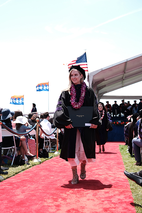 Beautiful candid graduation portrait of a female student walking outdoors