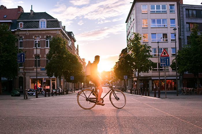 A lifestyle portrait of a man resting on a bicycle outdoors at sunset