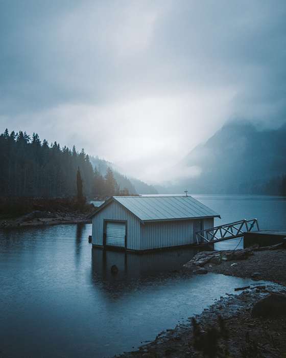 A boat shed in a lake among a beautiful mountainous landscape in blue light