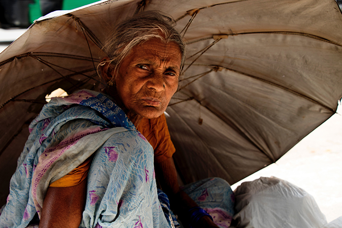 An old woman hiding under an umbrella from the sun - best quality light of day for portraits