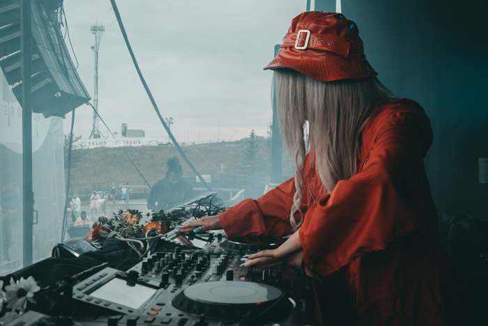 A portrait of a female dj playing onstage - festival photography