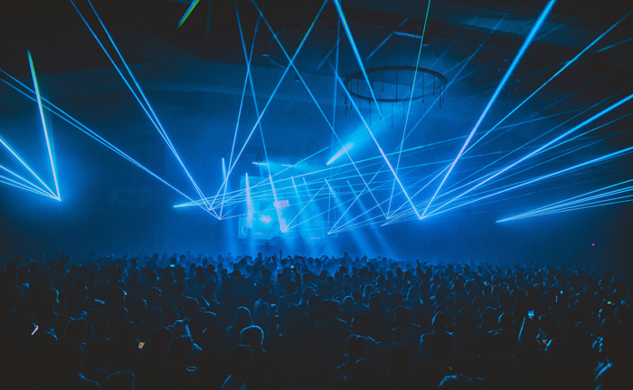 a large ground watching a concert in low light with blue strobes - music festival photography tips