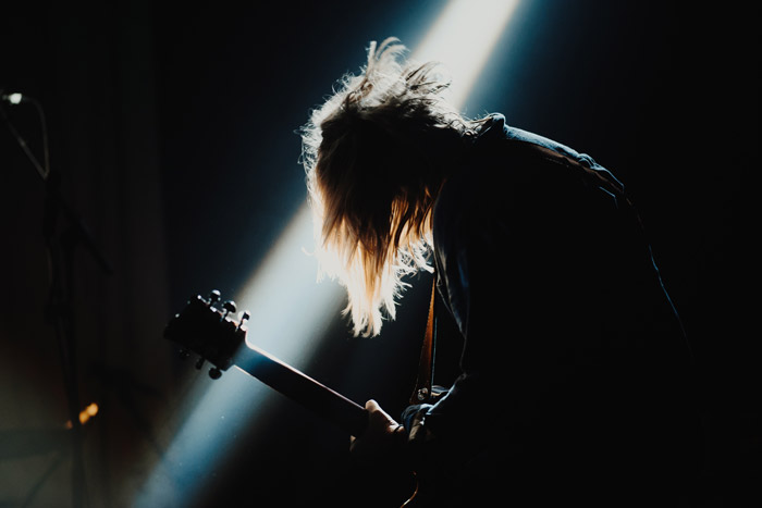 Atmospheric portrait of a performer onstage at a festival