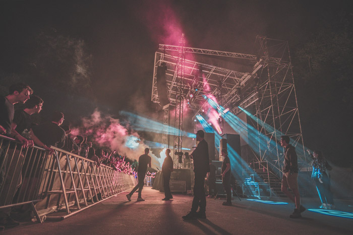 a large crowd watching a concert in low light - music festival photography tips