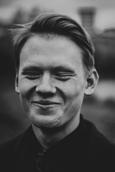 A black and white portrait of a man smiling natural - how to smile for pictures