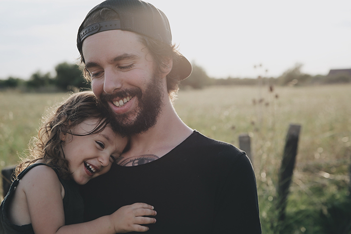 Sweet portrait of a smiling father and young daughter outdoors - how to smile for pictures