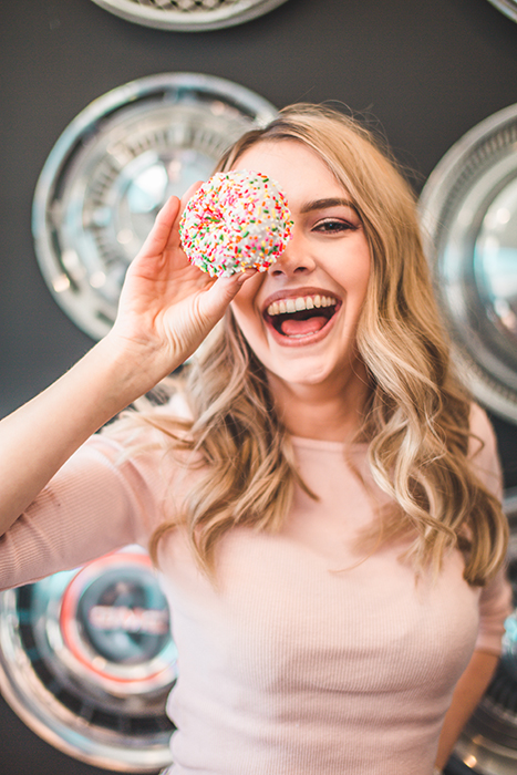 Fun portrait of a laughing female model holding a cake to her eye - how to smile for pictures