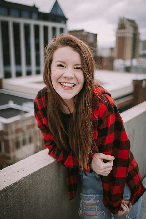 Fun portrait of a laughing female model posing on an urban rooftop - how to smile for pictures
