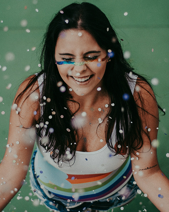 Fun portrait of a laughing female model covered in falling glitter - how to smile for pictures