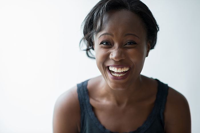 A woman laughing against a white background - smile for the camera tips