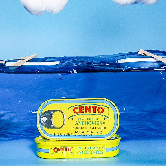 product shot of cans of anchovies on painted background - smartphone product photography