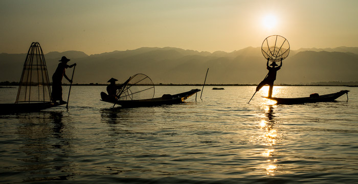 Serene shot of fishermen in a lake at sunset - how to remove glare in photos