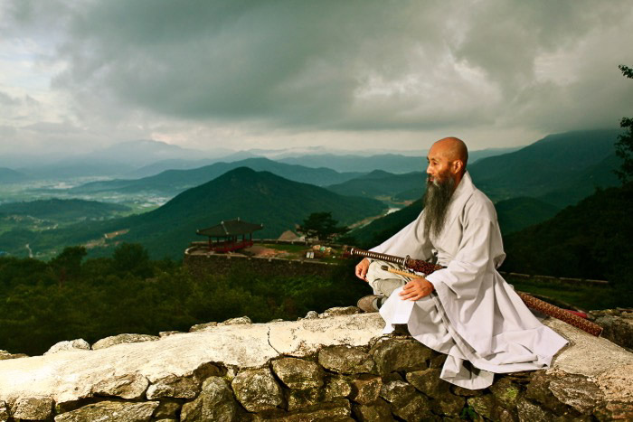 A monk sitting on a wallgazing off into the distance, with a beautiful mountainous landscape behind him - rule of space in photography