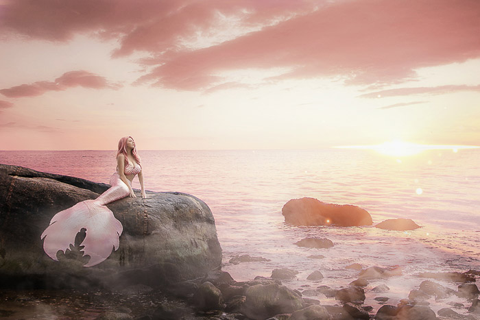 Dreamy self portrait boudoir photography of a female model posing in a mermaid tail by the sea