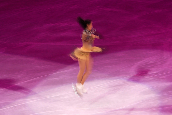 Blurry figure skating photography of a female skater twirling on the ice