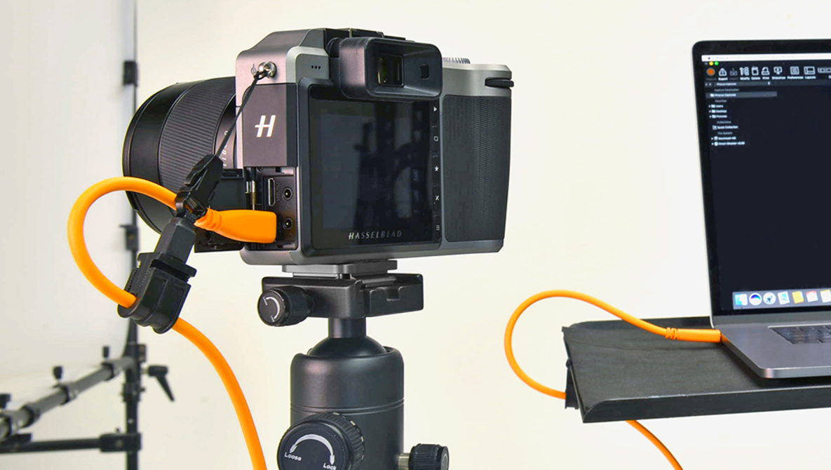 A DSLR camera tethered to a laptop - portable photo studio setup