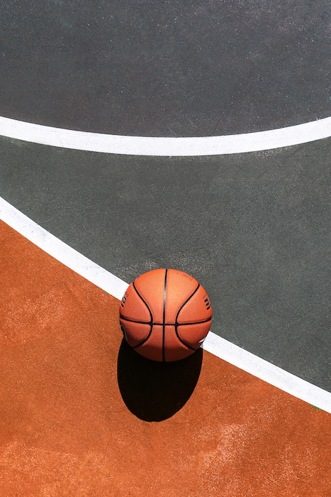 Cool composition of a basketball resting on a court - basketball photography tips