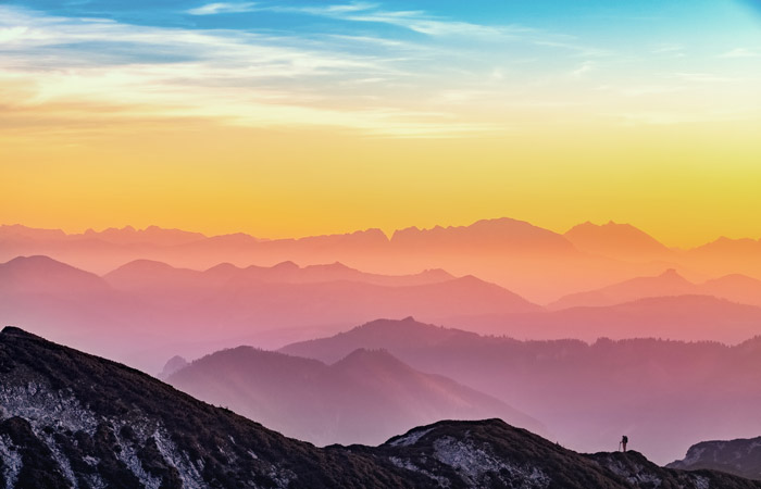 A mountainous landscape under a colorful sunset sky - color theory for landscape
