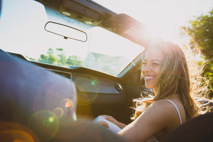 Portrait of a female model sitting in a car on a sunny day for summer photography ideas