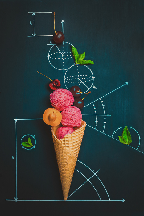 creative still life featuring ice cream and berries on a black board