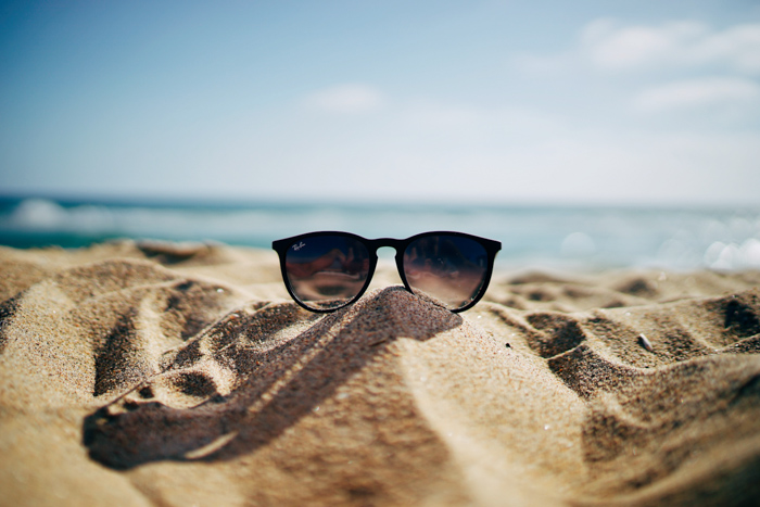 a pair of sunglasses on the beach - summer photography ideas