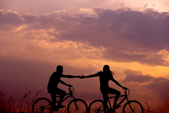 the silhouette of a couple on bikes at sunset in summertime