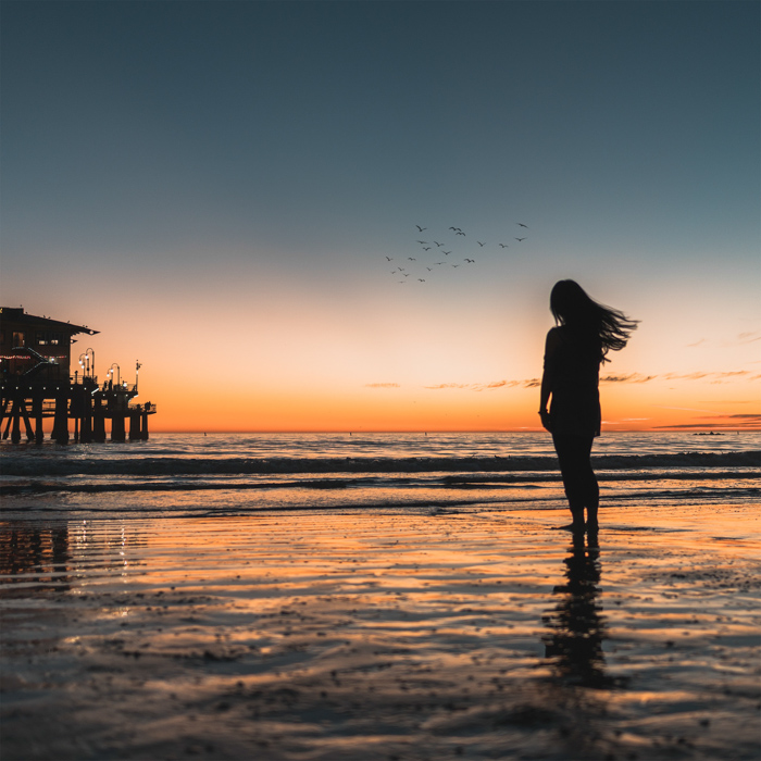 the silhouette of a female model standing on a beach at sunset in summertime