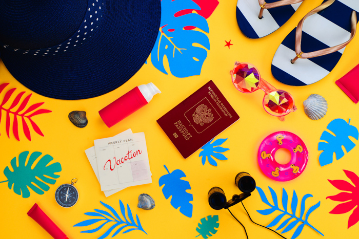 a summertime themed flat lay including travel items on yellow background