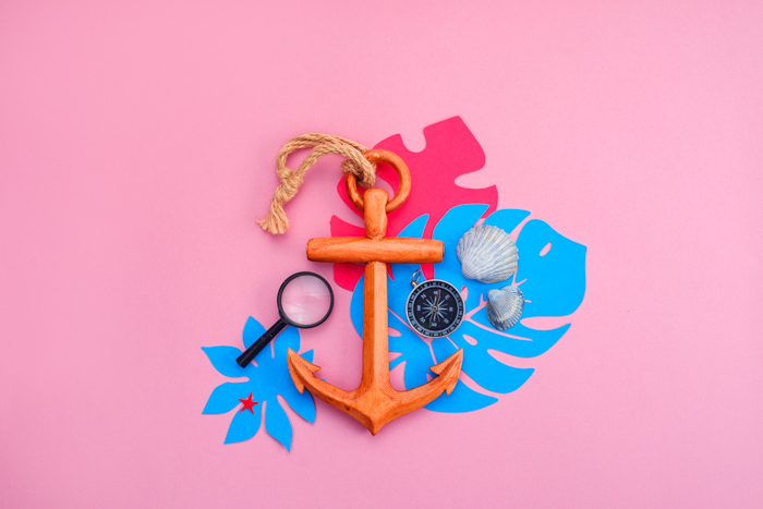Summertime themed flat lay including an anchor and shells on pink background