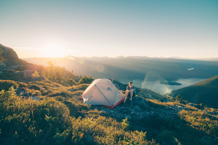 Creative summer portrait of a man sitting by a tent in a mountainous landscape