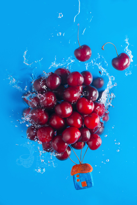 Creative still life featuring cherries on blue background for cool summer photography ideas