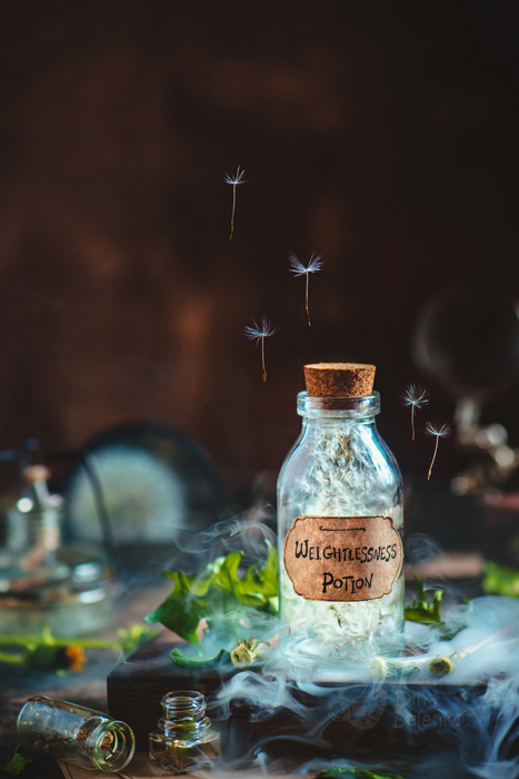 summer themed still life with dandelions and potion bottles