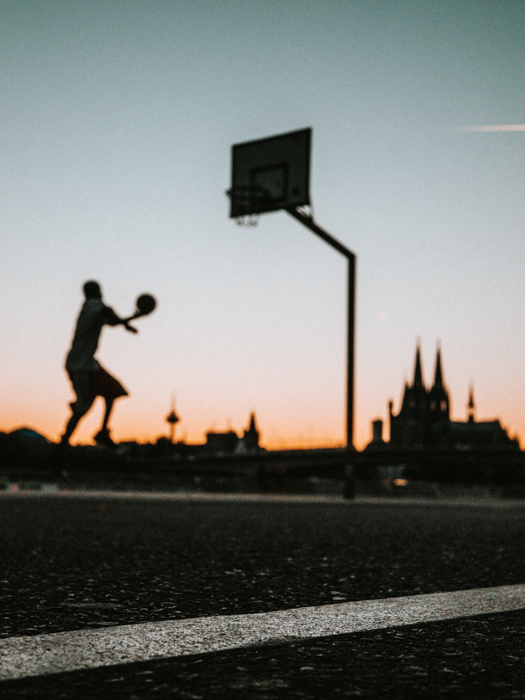 low angle shot of a basketball player on a summers day