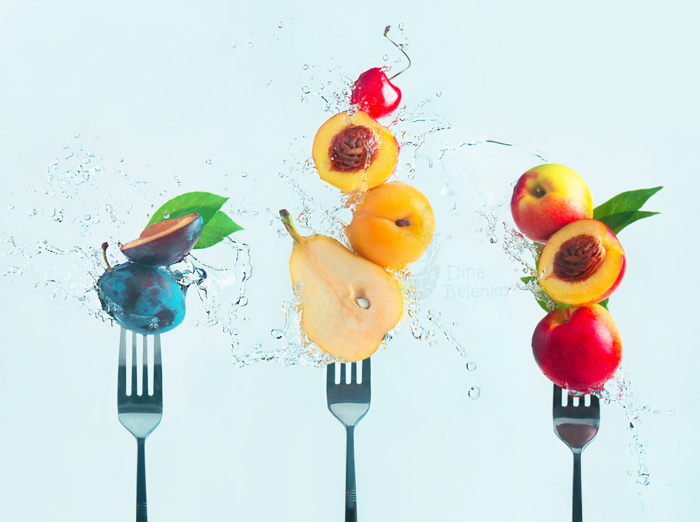 Cool still life featuring fruit on forks surrounded by water splashes