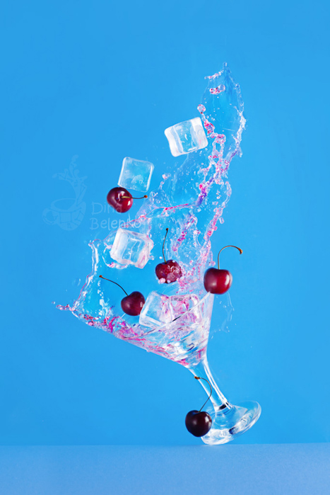 Cool summer themed still life featuring fruit , a cocktail glass and water splash
