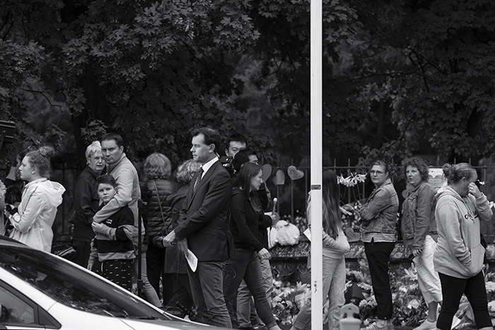 A news reporter at a floral tribute in Christchurch, New Zealand, following a terrorist attack.