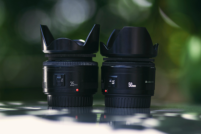 two camera lenses with lens hoods