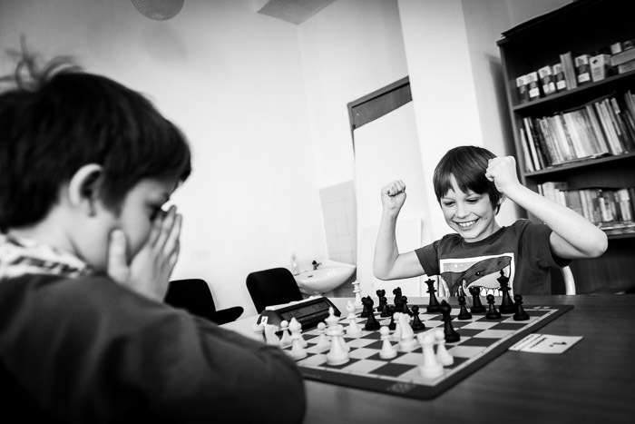 Monotone portrait of two boys playing chess outdoors