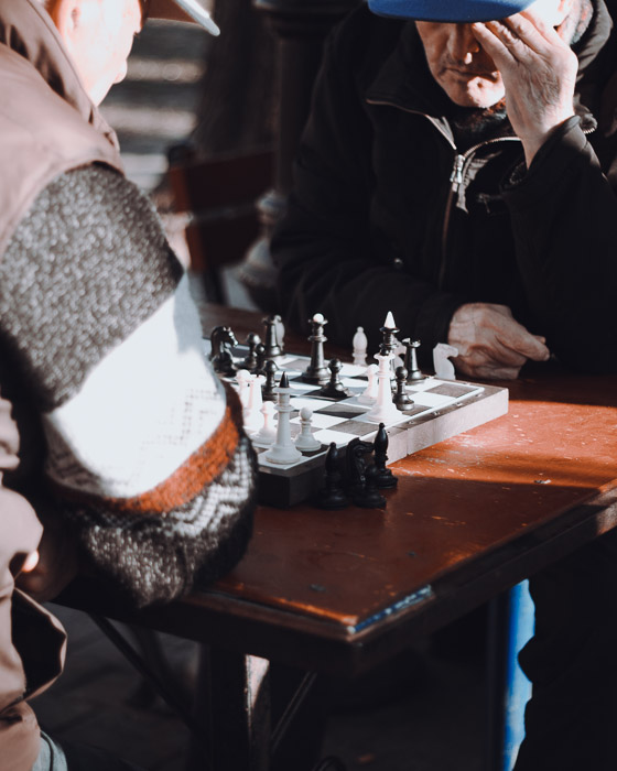 Two men playing chess outdoors