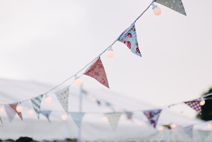 streams of pastel colored bunting outdoors in low light