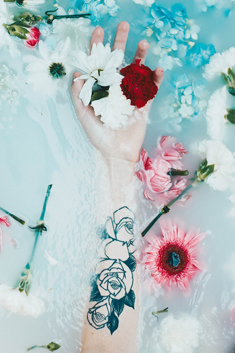 a tattooed arm and flowers in a milk bath