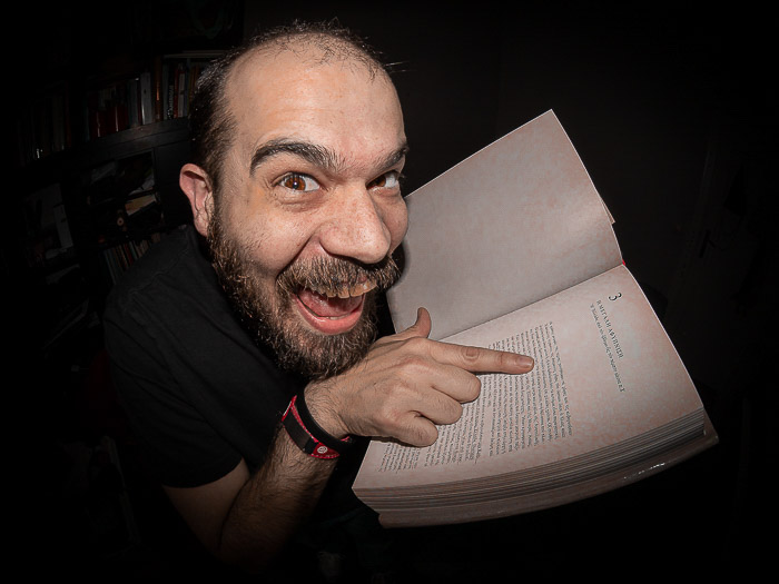 Humorous portrait of a man pointing to a book shot with a fisheye lens