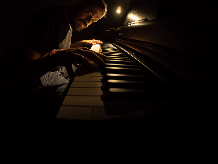 Atmospheric fisheye photo of a man playing piano in low light