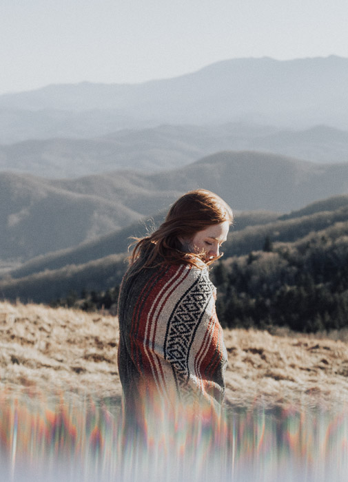 Artistic portrait of a femal model posing in a mountainous landscape taken using fractal filters