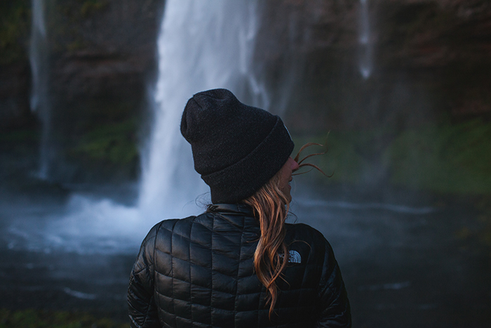 A female photographer in front of a waterfall in iceland