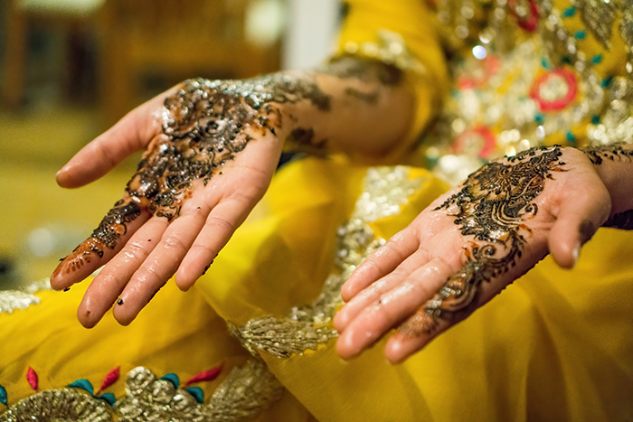 Beautiful wedding portrait of the decorated hands of an Indian bride posing in traditional costume - Indian wedding photography