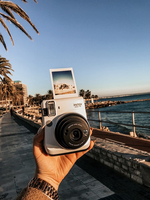 A persons hand holding an instax camera outdoors by the coast