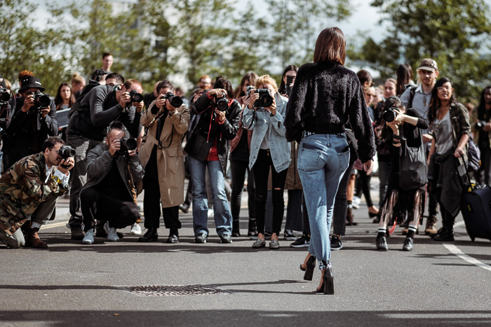 A group of photographers shooting a fashion portrait of a female model outdoors