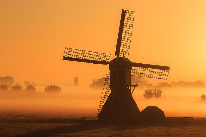 A windmill in a foggy landscape