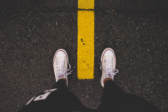 An overhead shot of a persons feet standing over a yellow line on the road